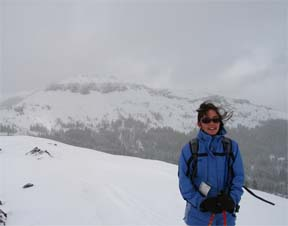 Image of skier on the summit of Andesite Peak on a stormy day with Castle Peak in the background.