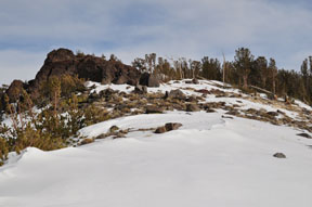 Image of red rock outcropping and spares snow on ridge