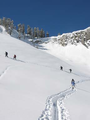 Image of skiers ascending the bowl below Horse Ridge