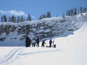 Image of skiers attaching climbing skins before final climb to top of Horse Ridge
