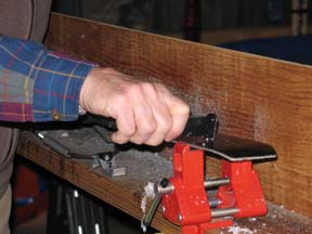 Image of scraping wax from the ski groove